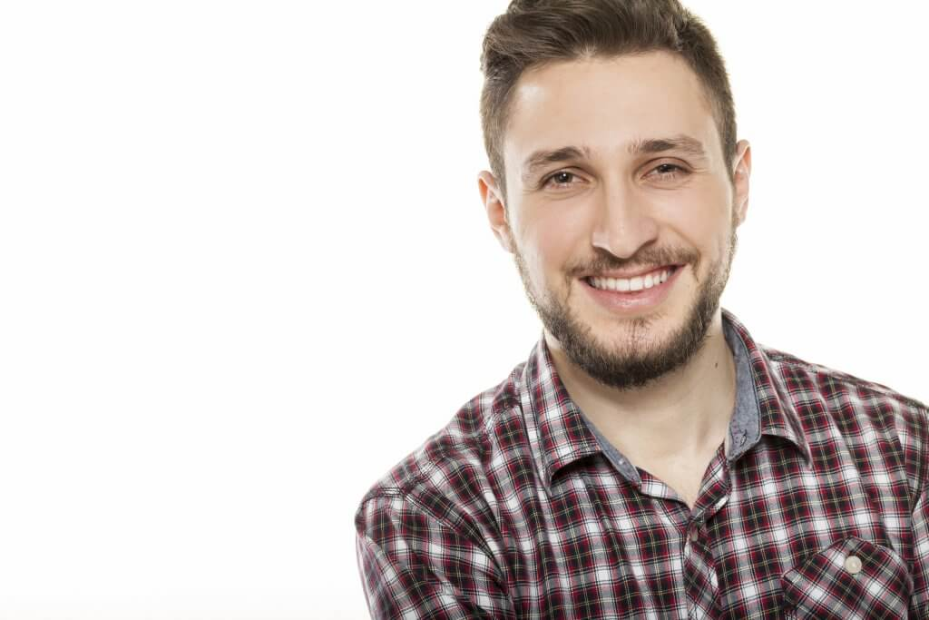 Happy young man posing on white background.