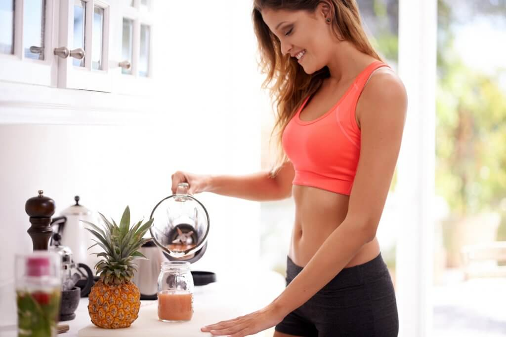 Shot of a sporty young woman pouring a smoothie into a glass